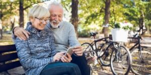 older couple looking at phone in park