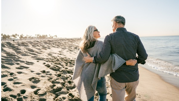 retired couple walking along beach