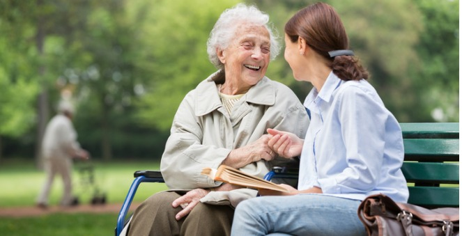 woman speaking to older woman on bench