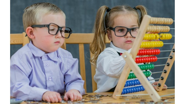 toddlers in glasses looking at abacus